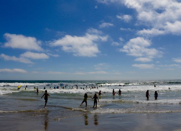 Children play in the waves of the Pacific Ocean at Santa Monica Beach
