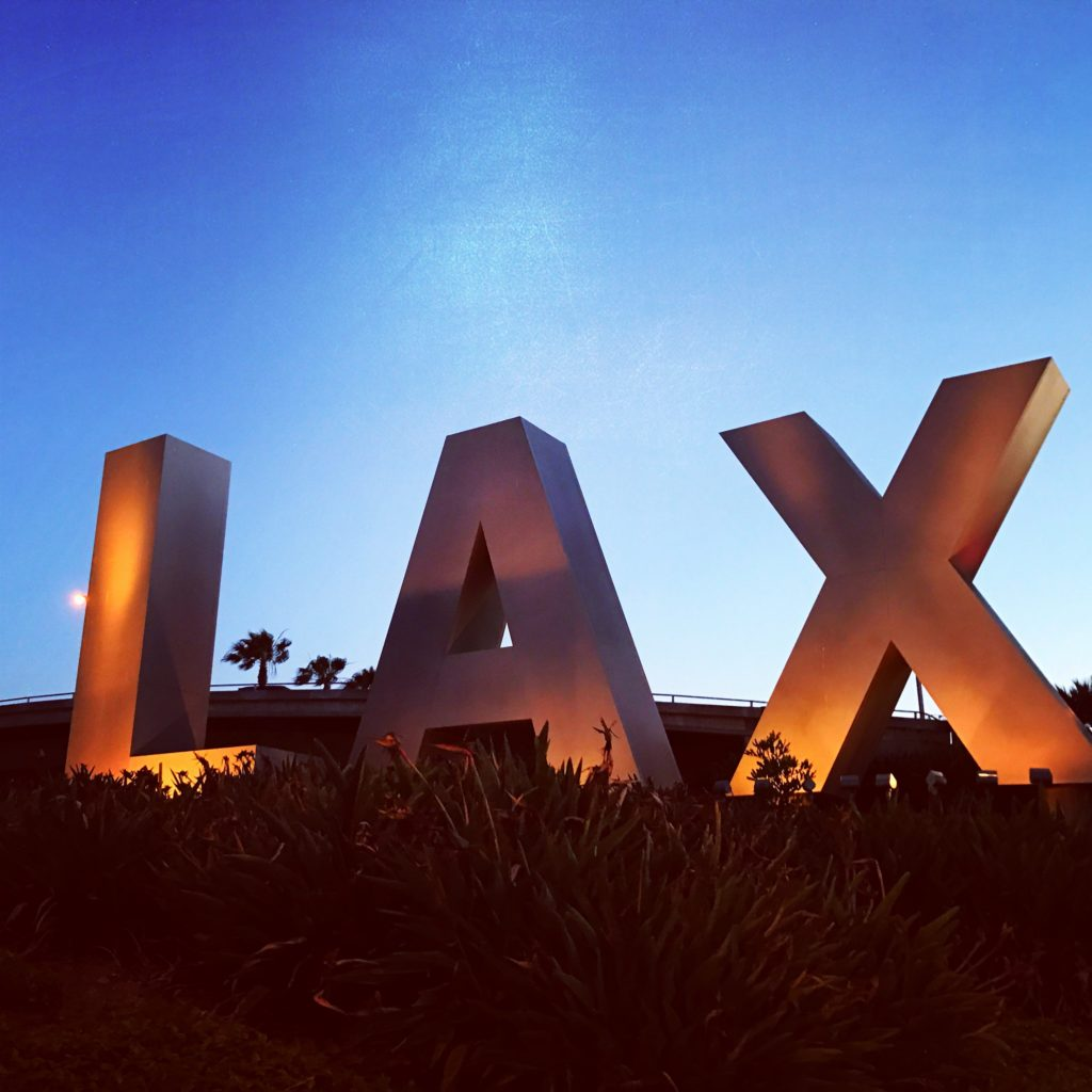 Dusk and the LAX sign welcome travelers to Los Angeles International Airport